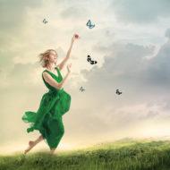 Beautiful girl following butterflies on a mountain