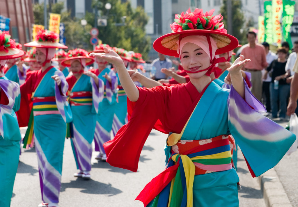 Japanese women wearing bright kimono dance in a parade